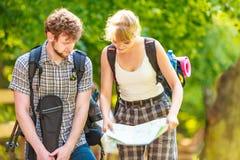 Caminhando o mapa backpacking da leitura dos pares na viagem Imagens de Stock Royalty Free
