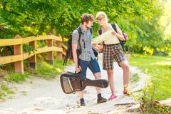 Caminhando o mapa backpacking da leitura dos pares na viagem Imagem de Stock Royalty Free