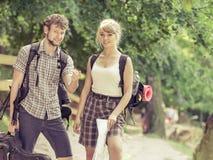 Caminhando o mapa backpacking da leitura dos pares na viagem Foto de Stock Royalty Free