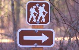 Caminhando o sinal com seta direcional Imagens de Stock