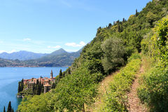 Caminhando o trajeto e o panorama da vila Varenna da beira do lago no lago Como com as montanhas em Lombardy Fotografia de Stock Royalty Free