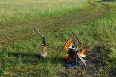 Caminhando a paisagem com fogueira, chaleira e um machado no boleto Ajardine com campo, estrada e céu de grama Fotografia de Stock