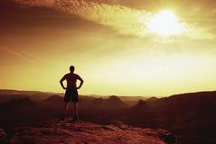Caminhante auto-confiante na pose do akkimbo no pico da rocha foto de stock
