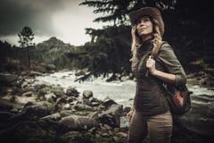 Caminhante bonito da mulher perto do rio selvagem da montanha fotografia de stock