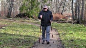 Caminhante cansado com as bengalas no trajeto no parque filme