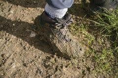 Caminhante com a bota enlameada na terra enlameada Imagem de Stock