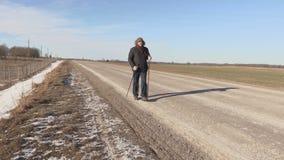 Caminhante com caminhada de polos que anda perto da estrada filme