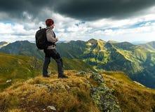 Caminhante com a trouxa em montanhas Fotos de Stock Royalty Free