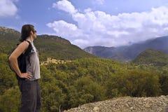 Caminhante com a trouxa pequena nas montanhas Fotografia de Stock