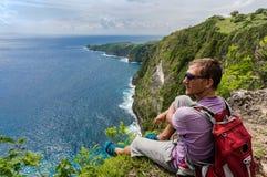 Caminhante com a trouxa que senta-se na parte superior da montanha Imagem de Stock Royalty Free