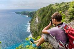 Caminhante com a trouxa que senta-se na parte superior da montanha e que faz a foto Imagens de Stock