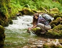 Caminhante da jovem mulher pelo rio Fotografia de Stock