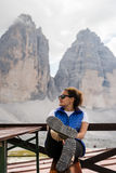 Caminhante da jovem mulher que descansa perto da formação de rocha famosa Tre Cime imagem de stock royalty free