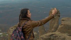 Caminhante da jovem mulher que toma a foto com o telefone esperto em video estoque