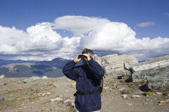 Caminhante da montanha que olha através dos binóculos Fotos de Stock