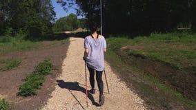 Caminhante da mulher com os polos de passeio do nordic no trajeto no parque vídeos de arquivo