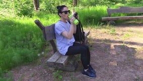 Caminhante da mulher com os polos de passeio do nordic que relaxam no banco vídeos de arquivo