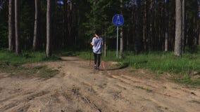 Caminhante da mulher com polos nórdicos que anda dentro ao parque video estoque