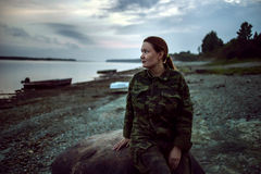 Caminhante da mulher dentro na roupa da camuflagem que senta-se na pedra na costa do rio Fotografia de Stock Royalty Free