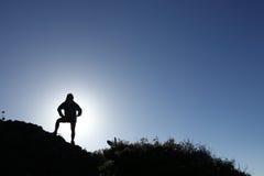 Caminhante da mulher na silhueta que está na montanha superior Fotografia de Stock Royalty Free