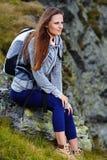 Caminhante da mulher que descansa em uma rocha Fotografia de Stock Royalty Free