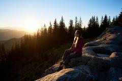 Caminhante da mulher que senta-se no pedregulho nas montanhas no por do sol fotografia de stock