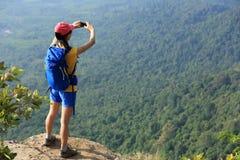 Caminhante da mulher que toma a foto com o telefone celular que caminha no pico de montanha fotografia de stock royalty free