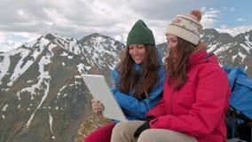 Caminhante das meninas com uma tabuleta que senta-se em uma rocha em um fundo das montanhas e dos lagos, Noruega vídeos de arquivo