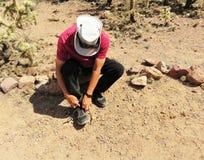 Caminhante do deserto que ajusta suas sapatas imagens de stock