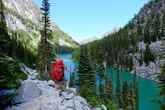 Caminhante do homem pelo lago alpino imagem de stock