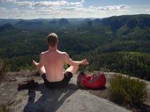 Caminhante do homem que senta-se na parte superior da montanha na pose da ioga fotos de stock