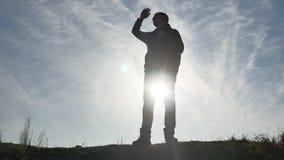 Caminhante do homem do turista da luz solar das silhuetas com trouxas que aprecia a opinião do por do sol da parte superior de um vídeos de arquivo