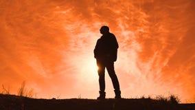 Caminhante do homem do turista da luz solar das silhuetas com trouxas que aprecia a opinião do por do sol da parte superior de um filme