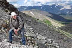 Caminhante do turista que descansa durante a escalada pesada na inclinação íngreme na montanha Fotografia de Stock Royalty Free