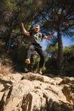 Caminhante em uma floresta que salta em rochas fotos de stock royalty free