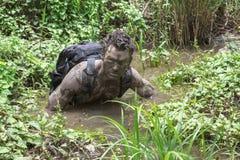 Caminhante enlameado que trekking através da água enlameada Imagens de Stock