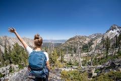 Caminhante fêmea com a trouxa ao longo da fuga do lago Sawtooth em Idaho Câmera traseira do revestimento Conceito para o curso e  fotografia de stock royalty free