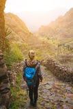 Caminhante fêmea com trouxa azul que fica na fuga trekking cobbled rochoso que conduz para baixo ao vale entre estéril imagens de stock royalty free