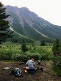 Caminhante fêmea que prepara uma refeição em sua elevação remota do acampamento em t fotos de stock