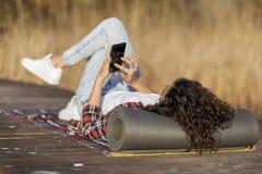 Caminhante fêmea que relaxa nas docas do lago fotografia de stock
