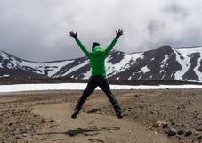 Caminhante feliz da mulher que salta no parque nacional de Tongariro imagem de stock