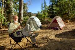 Caminhante idoso de sorriso no acampamento na floresta da manhã fotografia de stock