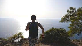 Caminhante masculino com a trouxa que alcança acima a parte superior da montanha e que salta mostrando emoções alegres Turista qu filme