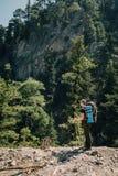 Caminhante masculino desportivo que trekking com a trouxa na floresta Fotografia de Stock Royalty Free