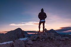 Caminhante masculino na paisagem vasta da montanha no por do sol fotografia de stock