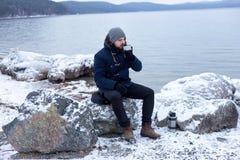 caminhante masculino que bebe o chá quente da garrafa térmica imagens de stock