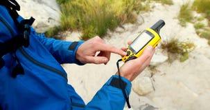 Caminhante masculino que usa o anemômetro digital para verificar o tempo 4k filme
