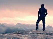 Caminhante na extremidade da rocha acima do vale Relógio do homem sobre o vale enevoado e nevoento imagens de stock