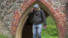 Caminhante nas madeiras com o PC da tabuleta nas paredes velhas do castelo video estoque