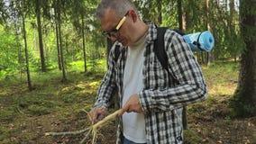 Caminhante nas madeiras com uma faca que aponta o ramo filme